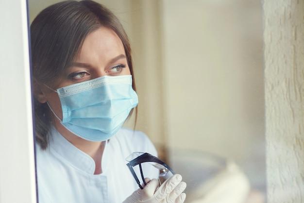 Доктор смотрит в окно во время пандемии коронавируса женщина в защитной маске