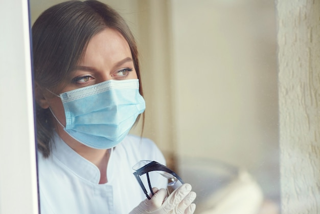 Doctor looking through the window during coronavirus pandemic female wearing protective mask