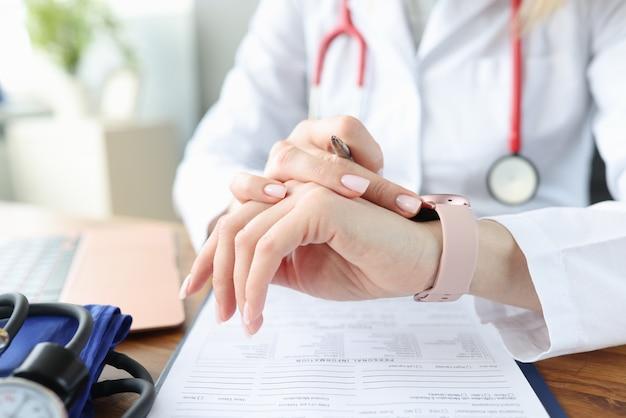 의사는 의료 사무실에서 작업 테이블에서 시계를 살펴 봅니다. 건강을위한 불규칙한 근무 시간