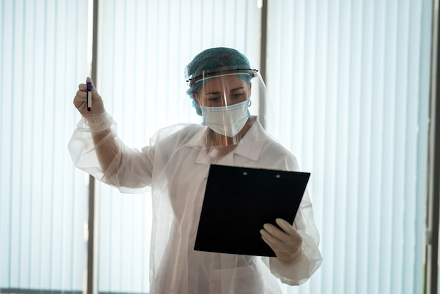 Doctor looks at the results of the laboratory test in the clipboard and holds a test tube with blood covid19