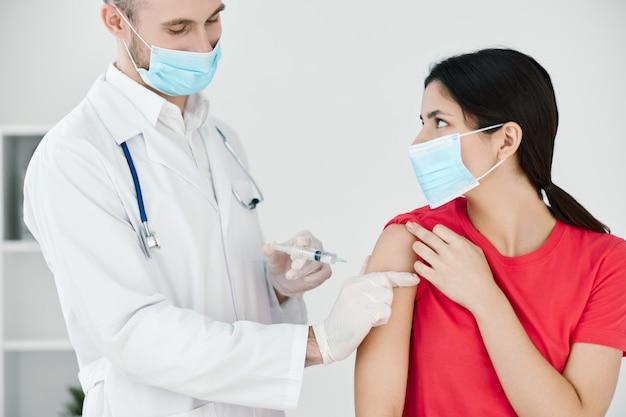 의사는 의료 마스크 계획으로 환자의 팔에 주사를