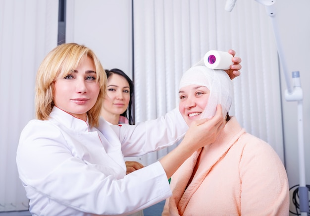 Doctor makes a bandage on head patient at clinic
