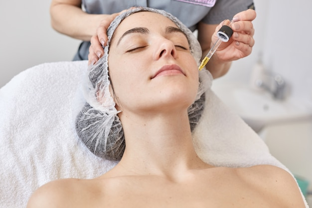 Doctor makes beautician procedure, applys vitamin serum to face of beautiful woman, client of cosmetology clinic. young female wants to improve her appearance with aethetic medicine. skin care concept