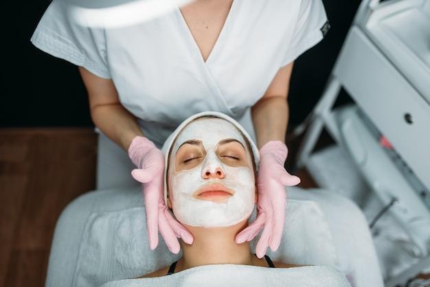 Врач делает маску для лица с кремом, пациентка