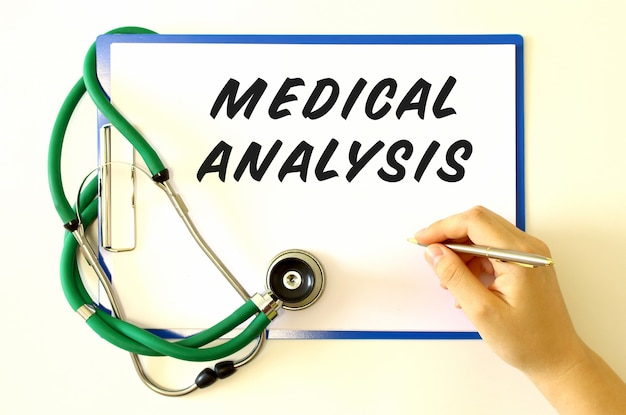 Doctor makes the inscription medical analysis. folder and stethoscope on a white surface.
