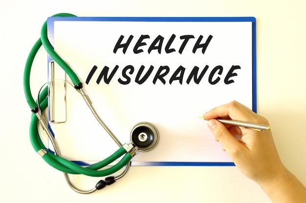医師は、文書に健康保険の碑文を作成します。フォルダーと聴診器。医療の概念。