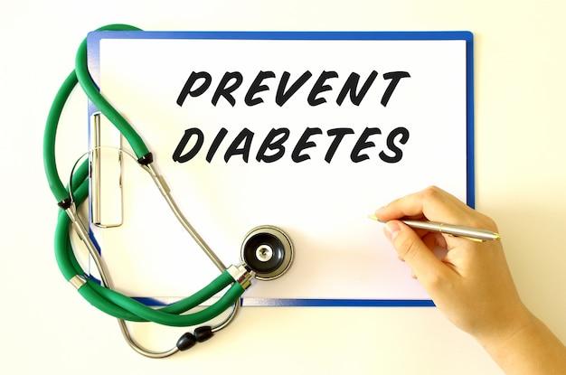 医師は、文書に「糖尿病を予防する」という碑文を作成します。白い表面上のフォルダーと聴診器