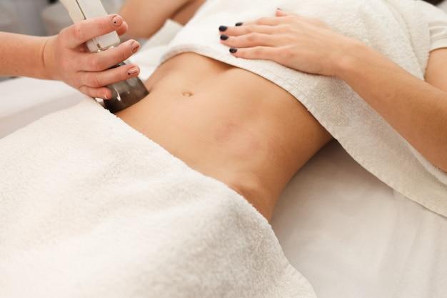 Doctor makes a vacuum massage procedure of the abdomen.