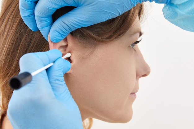 Doctor making ear test with cotton stick to a young woman.