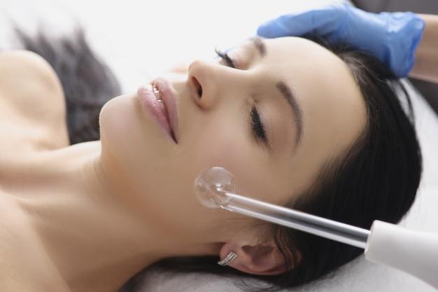 クリニックでダーソンバルの助けを借りて患者に顔のマッサージをする医師。