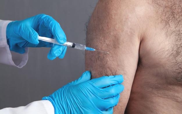 医師が患者に注射ワクチンを接種します。