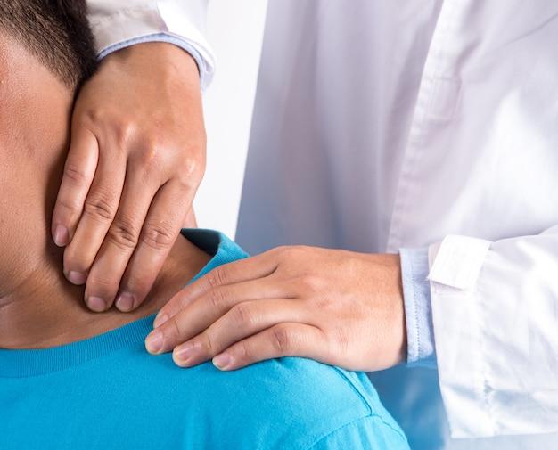 男性患者に首のマッサージを行う医師。