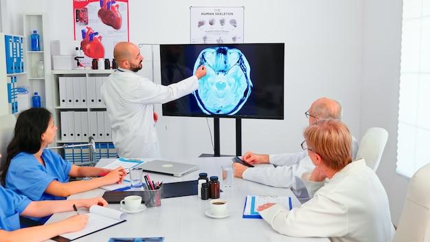 Врач делает презентацию медицинскому персоналу в зоне радиологии больницы с помощью монитора. клинический эксперт-терапевт беседует с коллегами о заболеваниях, диагностике, лечении пациентов.