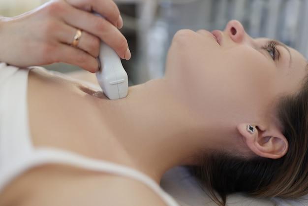 Врач делает узи щитовидной железы молодой женщине в клинике