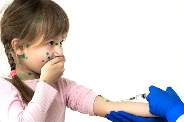 Doctor making vaccination injection to an afraid child girl sick with chickenpox, measles or rubella virus. vaccination of children at school concept.