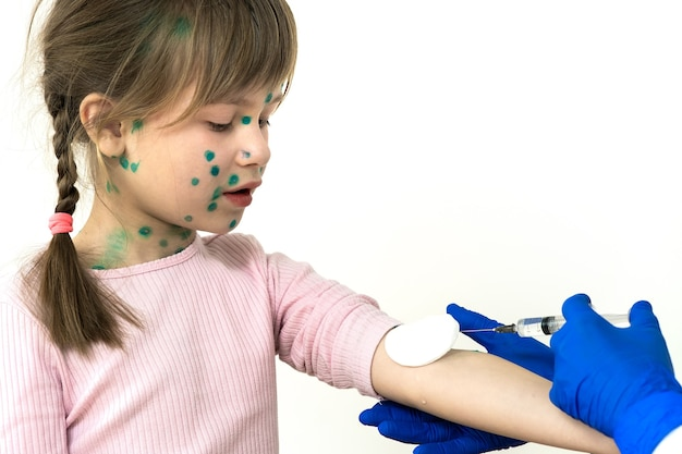 Doctor making vaccination injection to an afraid child girl sick with chickenpox, measles or rubella virus