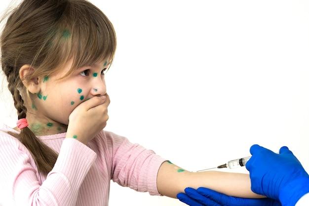 수두, 홍역 또는 풍진 바이러스에 걸린 두려운 아이 소녀에게 예방 접종 주사를하는 의사. 학교 개념에서 어린이의 예방 접종.