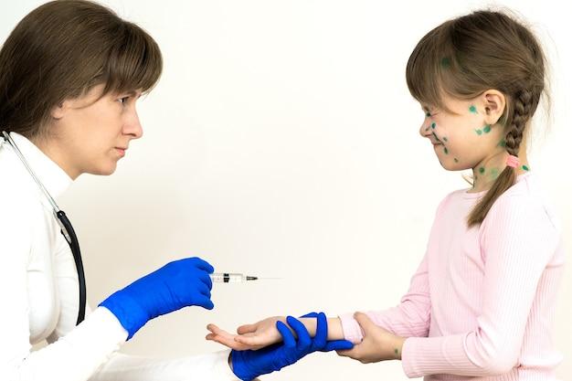 수두에 걸린 두려운 아이 소녀에게 예방 접종 주사를 만드는 의사