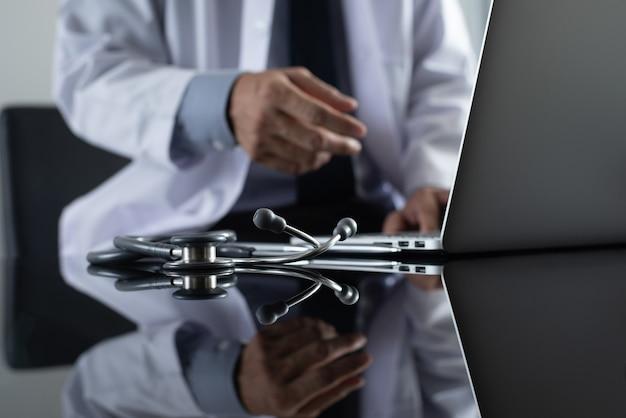 遠隔医療の概念のためのラップトップコンピューターを介してビデオ会議を行う医師