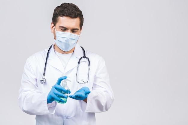 Человек доктора в изолированных перчатках маски стороны мантии. эпидемический пандемический вирус коронавируса 2019-ncov sars covid-19. бутылка со спиртовым жидким антибактериальным дезинфицирующим средством.