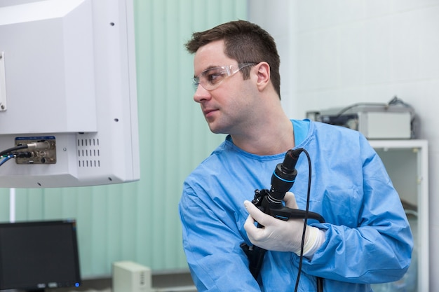 Врач мужчина в мониторе смотрит на результаты колоноскопии