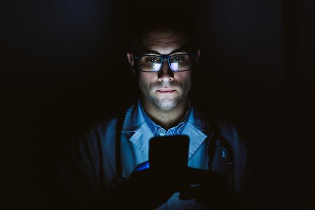 의사 남자 실내, 휴대 전화를 사용 하여입니다. 보호 장갑, 마스크 및 청진기를 착용하십시오. 코로나 바이러스 covid-19 개념