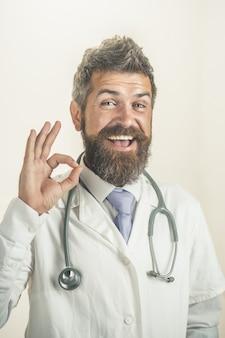 흰색 의료 가운에 목에 청진기를 가진 의사 남자 의사는 친절 한 제스처를 보여줍니다