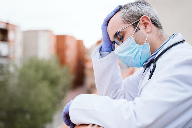 의사 남자 휴식, 피곤, 지친 또는 슬픈 찾고. 보호 장갑, 마스크 및 청진기를 착용하십시오. 코로나 바이러스 covid-19 개념