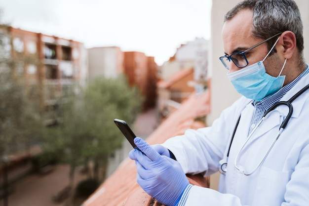 의사 남자 휴식, 휴대 전화를 사용 하여. 보호 장갑, 마스크 및 청진기를 착용하십시오. 코로나 바이러스 covid-19 개념