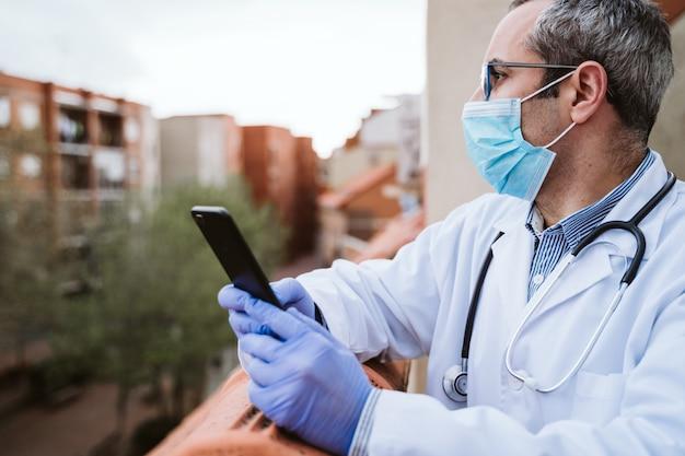의사 남자 휴식, 휴대 전화를 사용 하여. 보호 장갑, 마스크 및 청진기를 착용하십시오. 코로나 바이러스 Covid-19 개념 프리미엄 사진