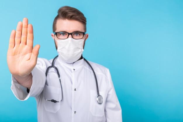 Доктор человек с помощью маски и открытой руки делает знак остановки