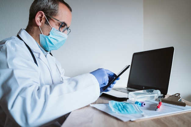 Doctor man working on laptop and mobile phone. corona virus test on table. covid-19 concept