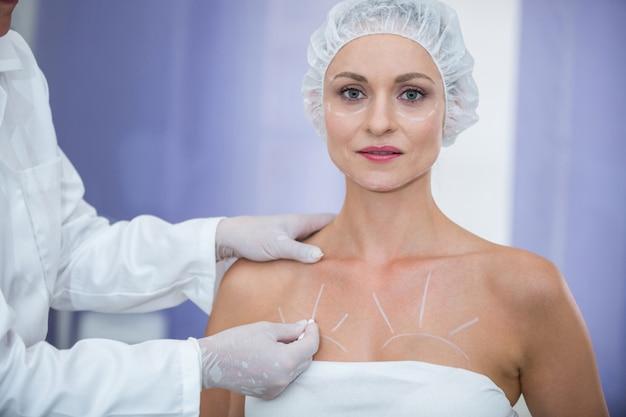 乳房手術の女性患者の体にマーキングする医師