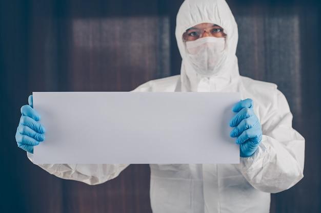 Un medico in maschera, guanti e tuta protettiva in possesso di carta bianca