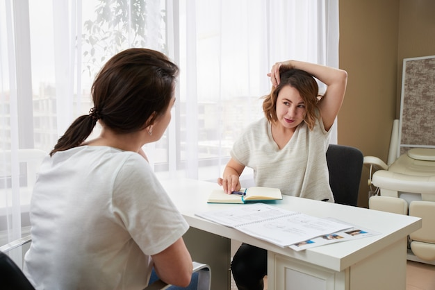 Doctor or massage specialist consulting young woman about headache