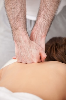 Doctor massaging the back of his patient while using the back of his hand
