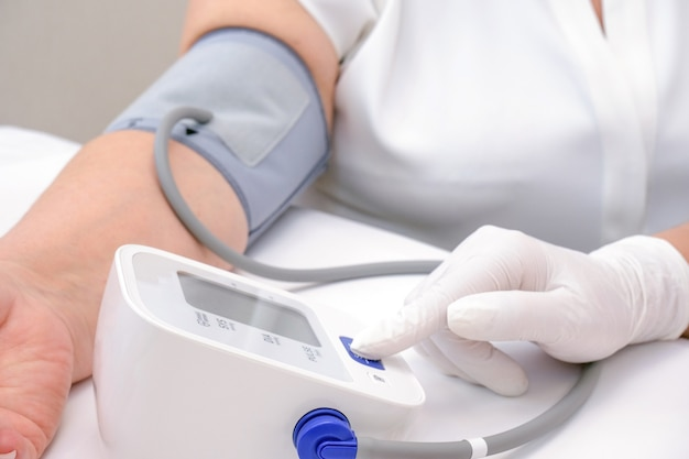 Doctor measures the blood pressure of an adult person
