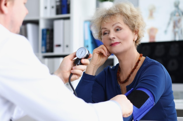 Врач измеряет кровяное давление пожилой женщины