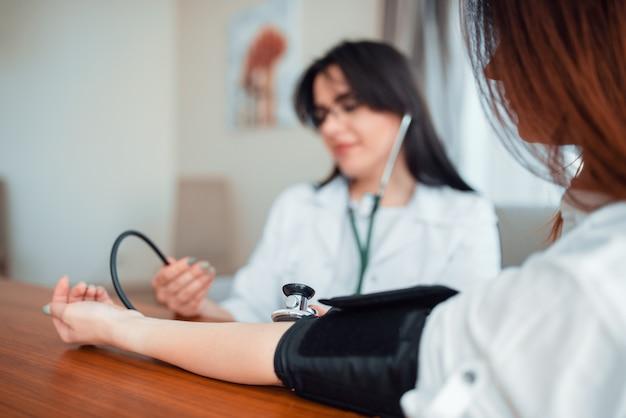 医者は若い母親の体圧を測定します