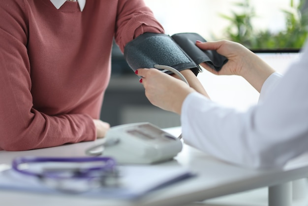 Doctor measures patient's blood pressure at appointment. medical care concept