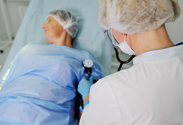 Doctor measures the patient tonometer pressure against the surface of a surgical operating room. preparation for surgery