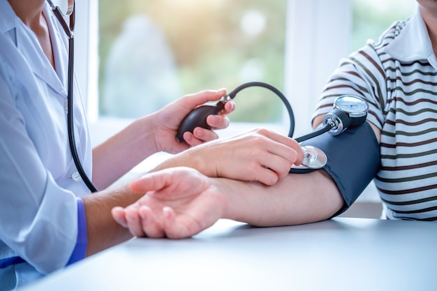 Doctor measures the pressure of the patient during a medical examination and consultation in the hospital.