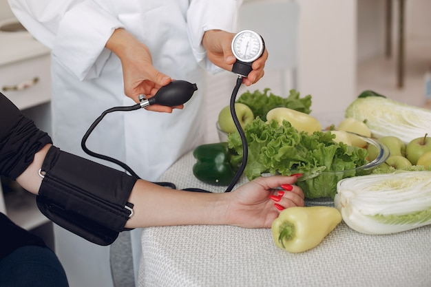 Doctor measures the pressure of the patient in the kitchen