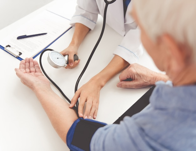 Doctor measures pulse in grandfather's clinic