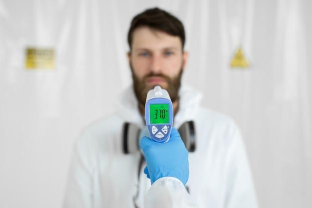 의사는 전염병의 동료에게 적외선 온도계로 온도를 측정합니다. 실험실 외 투에 남자 의사 과학자의 초상화. 코로나 바이러스의 개념