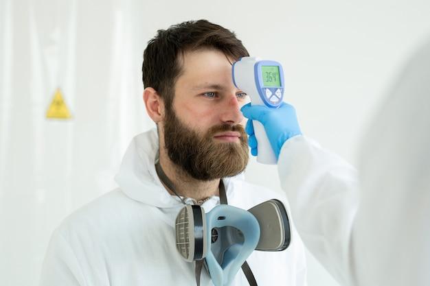 의사가 적외선 온도계를 사용하여 감염병 동료에게 온도를 측정합니다.