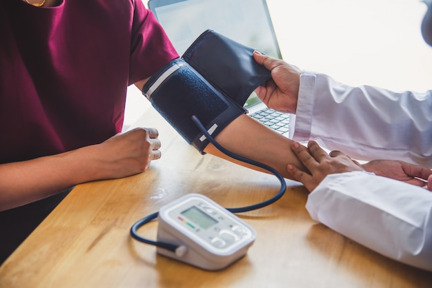 Doctor measuring blood pressure from her patient