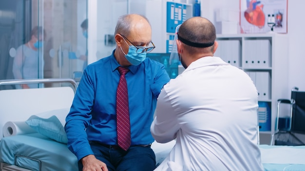 Doctor measuring blood pressure to senior old retired man patient during covid-19 healthcare crisis global pandemic in modern private hospital or clinic. wearing protective equipment examination room
