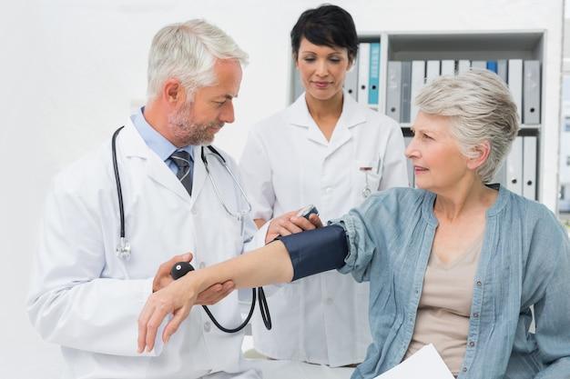 Doctor measuring blood pressure of a senior patient