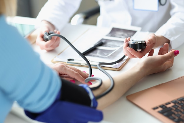 Doctor measuring blood pressure of woman in clinic closeup